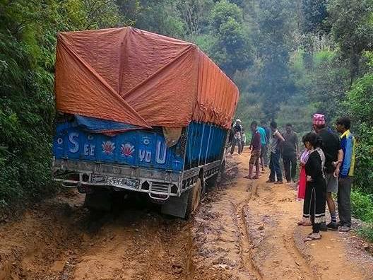 雨でぬかるんだ道に車輪をとられたトラック
